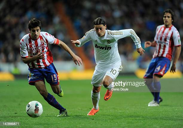 Mesut Ozil of Real Madrid CF chases the ball with Roberto Canella of Real Sporting de Gijon during the La Liga match between Real Madrid CF and Real...