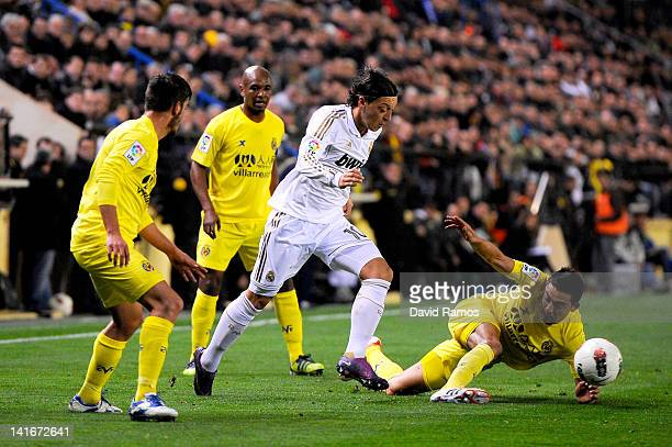 Mesut Ozil of Real Madrid CF duels for the ball with Bruno Soriano of Villarreal CF , Joan Oriol of Villarreal CF and Marcos Senna of Villarreal CF...