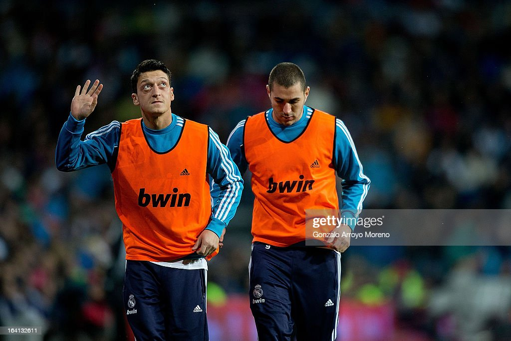 Mesut Ozil (L) of Real Madrid CF greets the supporters while warming-up with team-mate Karim Benzema during the La Liga match between Real Madrid CF and RCD Mallorca at Santiago Bernabeu Stadium on March 16, 2013 in Madrid, Spain.