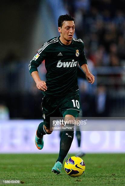 Mesut Ozil of Real Madrid CF runs with the ball during the La Liga match between Malaga CF and Real Madrid CF at La Rosaleda Stadium on December 22...