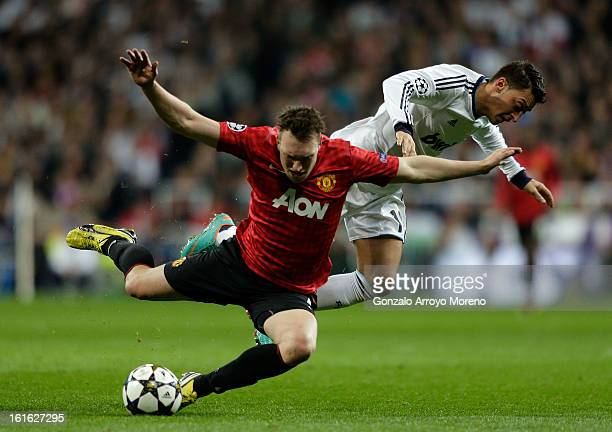 Mesut Ozil of Real Madrid clashes with Phil Jones of Manchester United during the UEFA Champions League Round of 16 first leg match between Real...