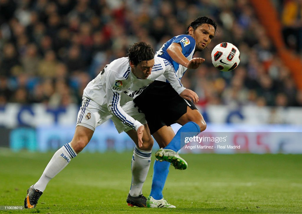 Mesut Ozil of Real Madrid duels for the ball with Abel Aguilar of Hercules during the La Liga match between Real Madrid and Hercules at Estadio Santiago Bernabeu on March 12, 2011 in Madrid, Spain.