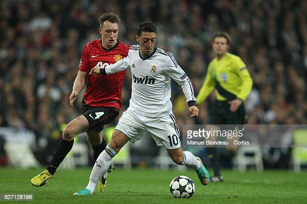 Mesut Ozil of Real Madrid duels for the ball with Phil Jones of Manchester United during the UEFA Champions League Round of 16 match between Real...