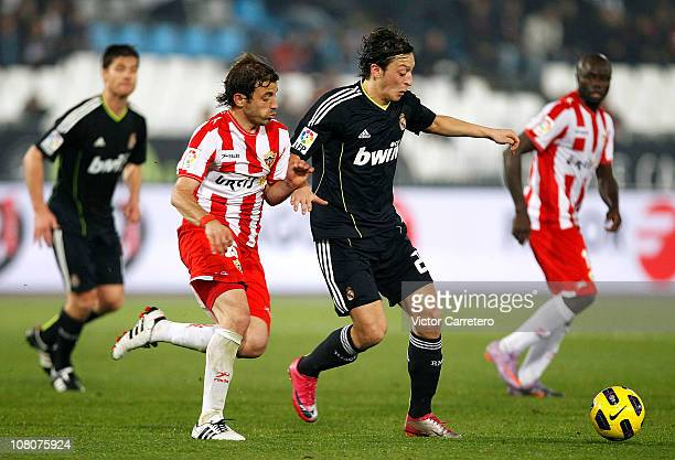 Mesut Ozil of Real Madrid fights for the ball with Hernan Bernardello of Almeria during the La Liga match between UD Almeria and Real Madrid at...