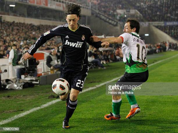Mesut Ozil of Real Madrid fights for the ball with Pedro Munitis of Racing Santander during the La Liga match between Racing Santander and Real...