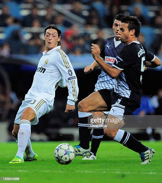 Mesut Ozil of Real Madrid is tackled by Adrian Calello of Dinamo Zagreb during the UEFA Champions League group D match between Real Madrid and Dinamo...