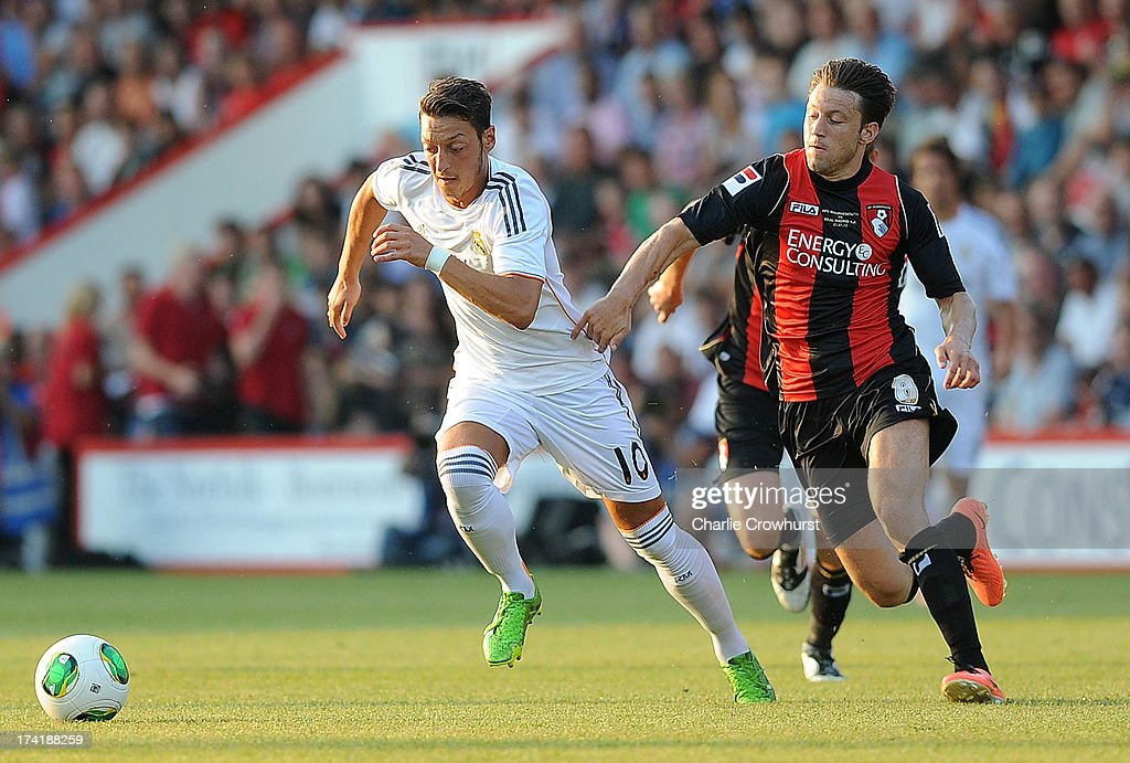 Mesut Ozil of Real Madrid looks to get away from Harry Arter of Bournemouth during the pre season friendly match between Bournemouth and Real Madrid at Goldsands Stadium on July 21, 2013 in Bournemouth, England,