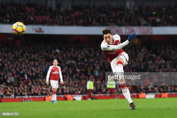 Mesut Ozil scores a goal for Arsenal during the Premier League match between Arsenal and Newcastle United at Emirates Stadium on December 16 2017 in...