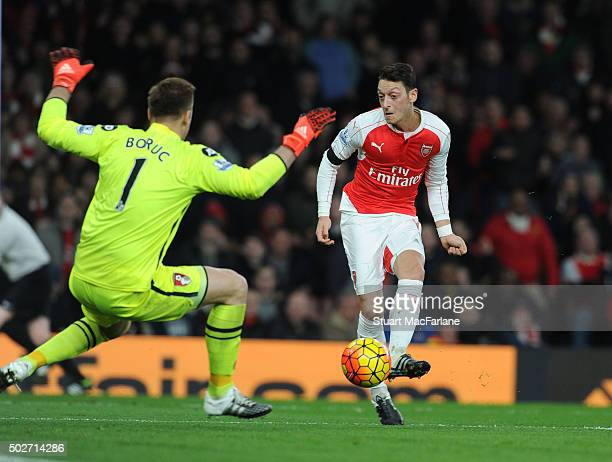 Mesut Ozil shoots past Bournemouth goalkeeper Artur Bouruc to score the 2nd Arsenal goal during the Barclays Premier League match between Arsenal and...