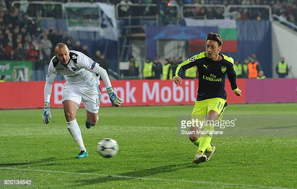 Mesut Ozil shoots past Ludogorets goalkeeper Milan Borjan to score the 3rd Arsenal goal during the UEFA Champions League match between PFC Ludogorets...
