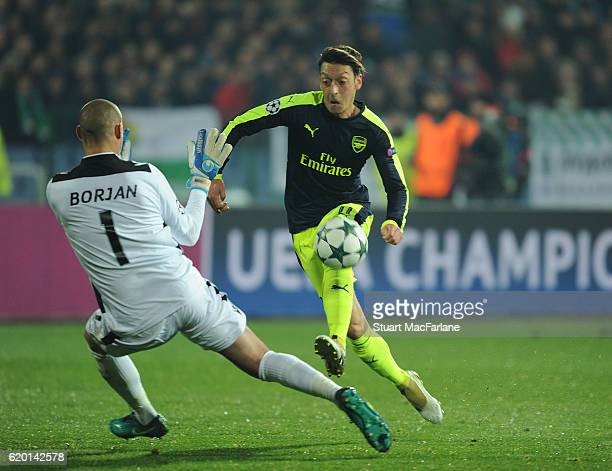 Mesut Ozil takes the ball past Ludogorets goalkeeper Milan Borjan to score the 3rd Arsenal goal during the UEFA Champions League match between PFC...