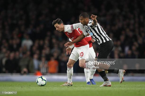 Mesut zil of Arsenal battles with Jos Salomn Rondn of Newcastle United during the Premier League match between Arsenal and Newcastle United at the...