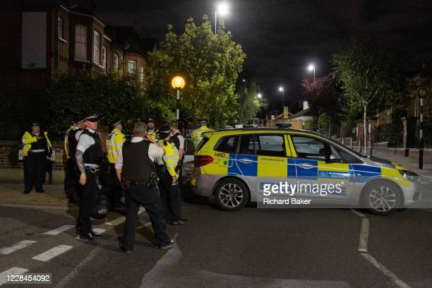 Met Police officers at the closed-off roads surrounding Herne Hill and Carnegie Library in Lambeth, after two people were reported shot in this...