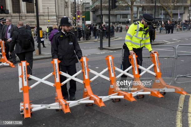 Met police officers drag into place antiterrorism security barriers called 'Pitagone F18' a rapid deployable Hostile Vehicle Mitigation System made...