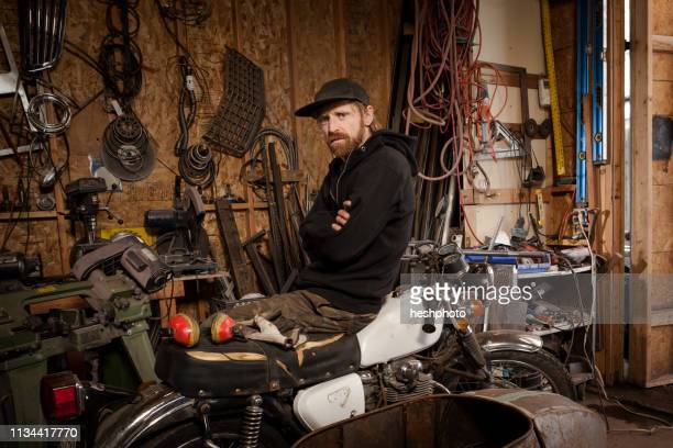 a metal artist and machine builder in his workshop - heshphoto stock pictures, royalty-free photos & images