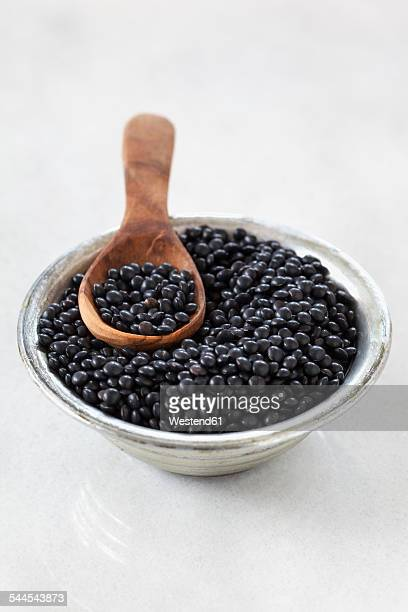 Metal bowl and wooden spoon of beluga lentils on white ground