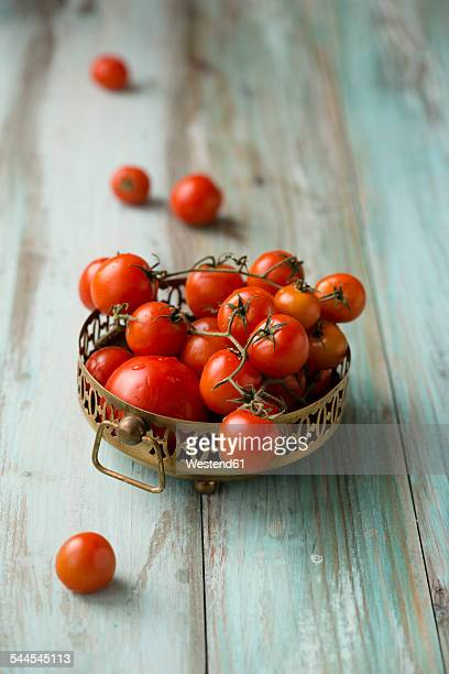 Metal bowl of cherry tomatoes on wood