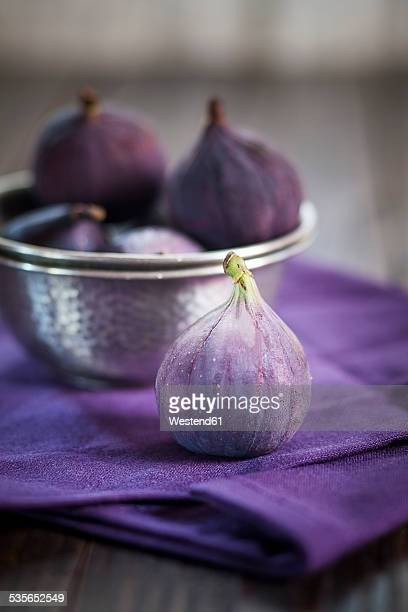 Metal bowl of figs on cloth