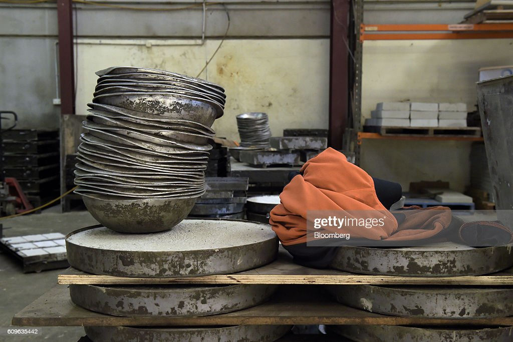 Metal bowls sit on top of stacked concrete molds at the