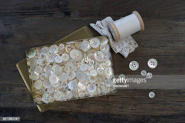 Metal box of different old mother-of-pearl buttons on dark wood