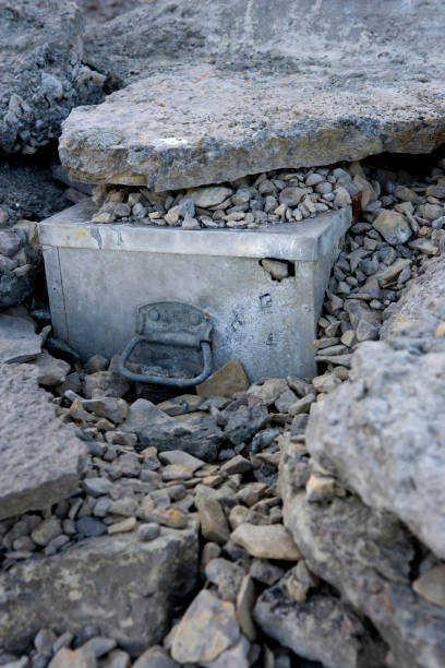 A metal box unearthed on a rocky beach