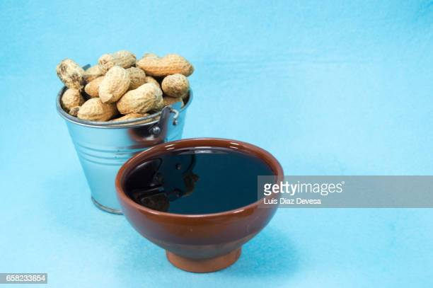 metal bucket filled with snacking peanuts - manchado stock pictures, royalty-free photos & images