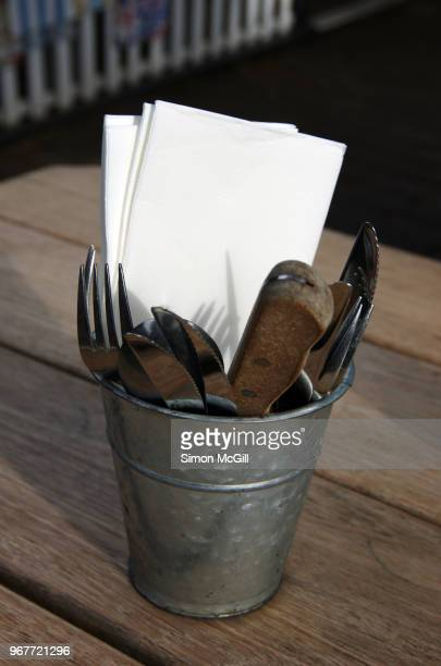 metal bucket of eating utensils and paper napkins on a wooden picnic table at a sidewalk cafe - paper napkin stock photos and pictures