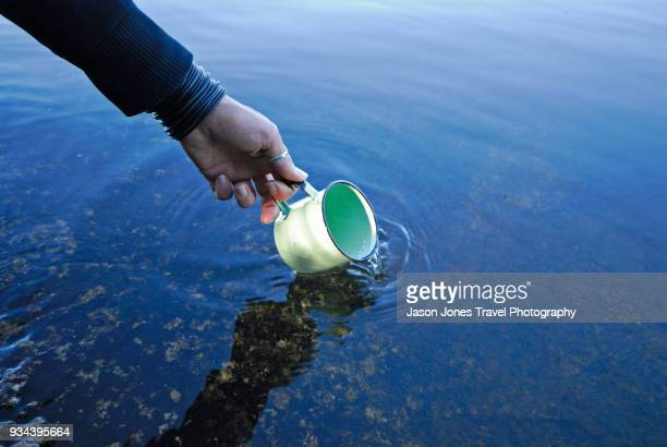 A metal camp cup gets filled with fresh, clear lake water