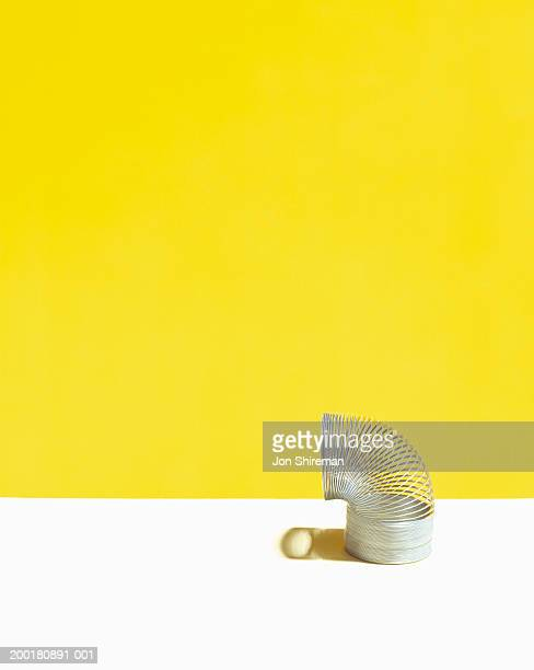 metal coil on white surface (digital enhancement) - metal coil toy stock photos and pictures