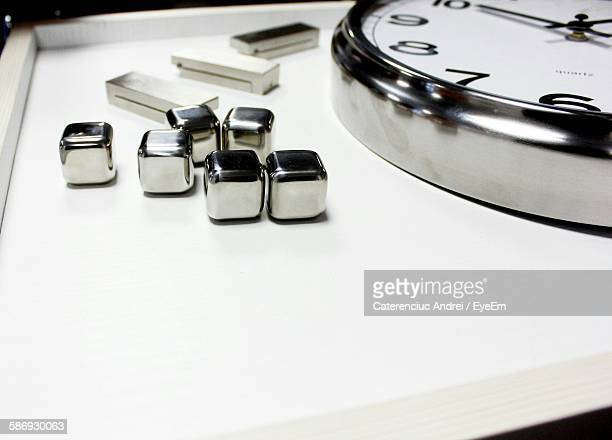 Metal Cubes By Wall Clock On Table
