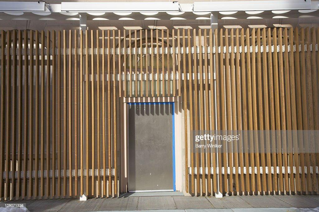 Metal Door Surrounded By Modern Vertical Wood Slat Design