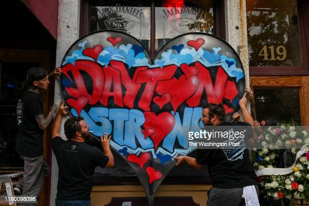 Metal fabricator Nick Bruno Kyle Knox James Bunn and Jason Phillips hang a metalfabricated Dayton Strong sign on the front of Ned Pepper's Bar at the...