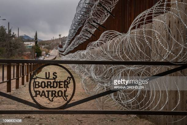 TOPSHOT A metal fence marked with the US Border Patrol sign prevents people to get close to the barbed/concertina wire covering the US/Mexico border...