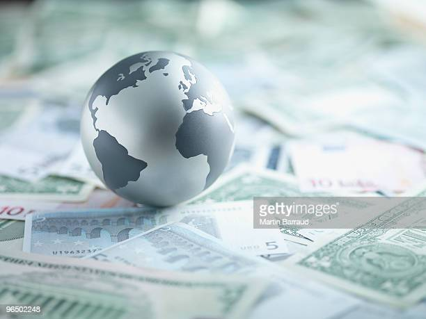 metal globe resting on paper currency - global stock pictures, royalty-free photos & images