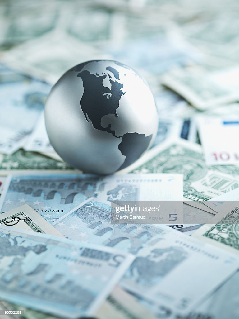 Metal globe resting on paper currency : Stock Photo