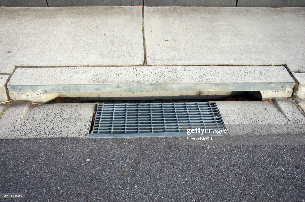 Metal Grate And Concrete Street Drain On The Sidewalk Of A Road Stock Photo