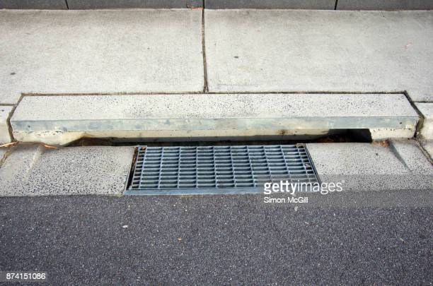 Metal grate and concrete street drain on the sidewalk of a road