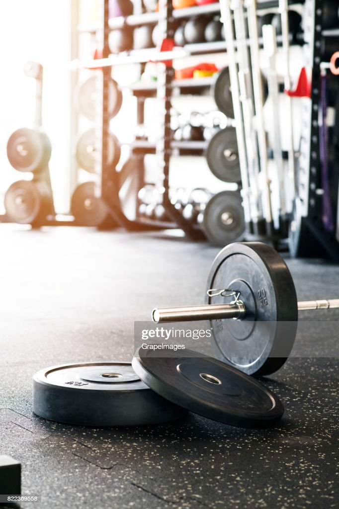 Metal heavy barbell laid on the floor in modern gym. : Stock Photo