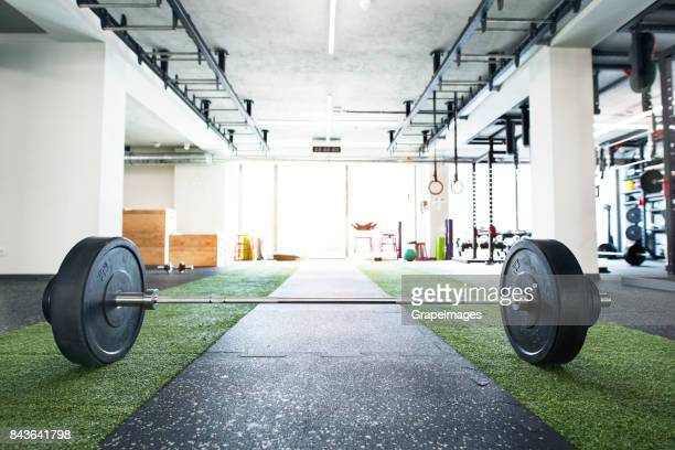 metal heavy barbell laid on the floor in modern gym. - barbell stock pictures, royalty-free photos & images