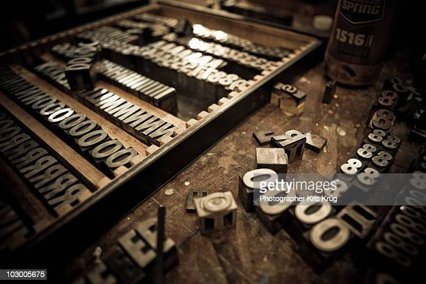Metal Letter Blocks Scattered on Wooden Table