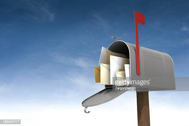 A metal mailbox filled with letters against the sky