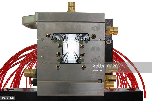 Metal mold extruding red plastic