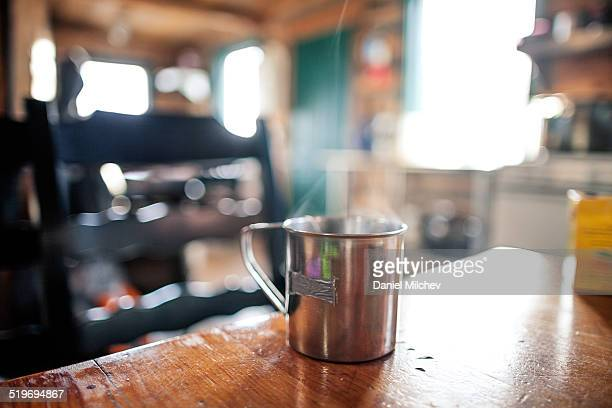 Metal mug on the table at a mountain house.