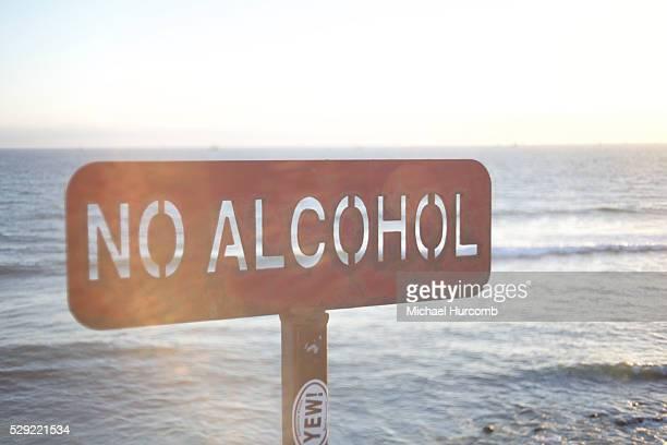 A metal 'No Alcohol' sign at the Pacific Ocean near Malibu California