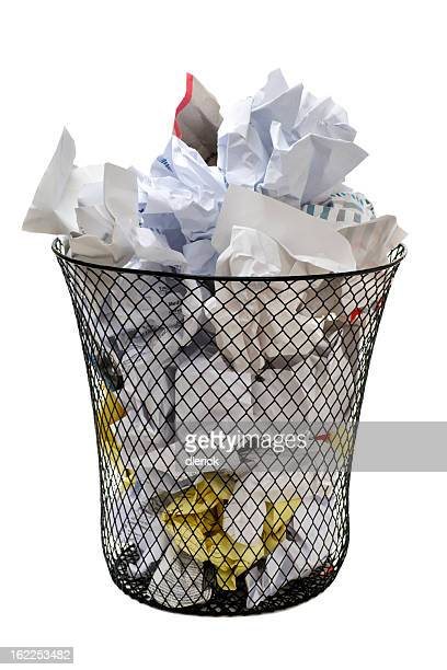Metal patterned waste basket overflowing with crumpled paper