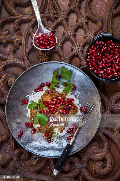 Metal plate of Khoresht Fesenjaan garnished with pomegranate seed