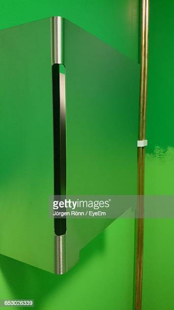 Metal Poles Over Green Wall For Display At Art Exhibition