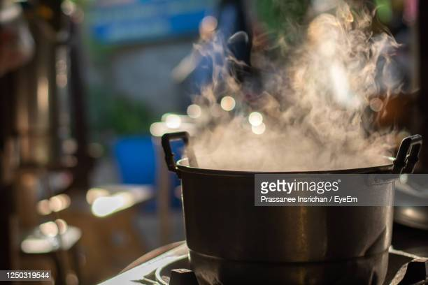 metal pot boil soup on gas stove with smoke in thai kitchen. make food for breakfast. - saucepan stock pictures, royalty-free photos & images