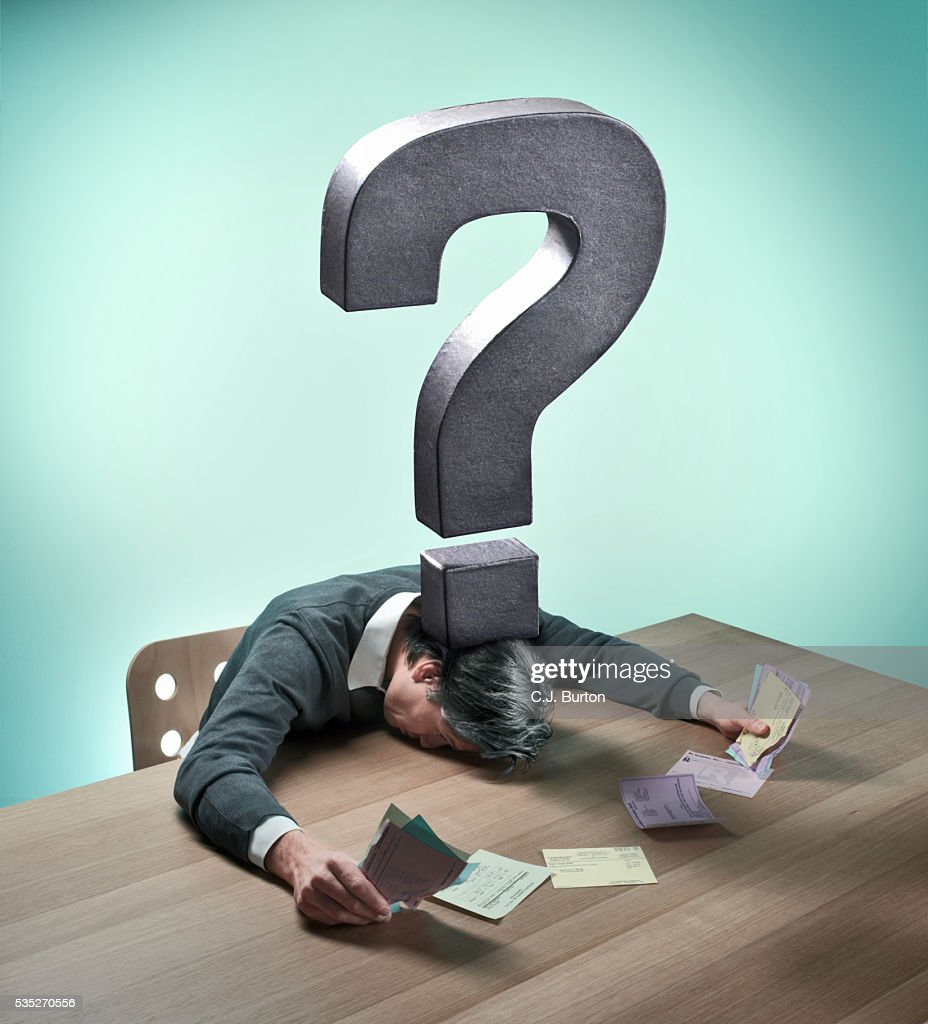 Metal question mark over man holding bills : Stock Photo