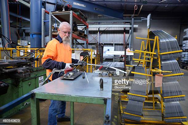 Metal rods used to shape car door panels are pressed by hand on the production line at the Backwell IXL plant in Geelong Australia on Tuesday May 20...